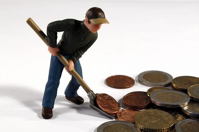 Eine männliche Figur schaufelt Kleingeld