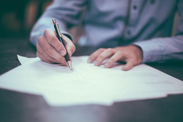 Ein Mann macht handschriftliche Notizen auf einem Zettel