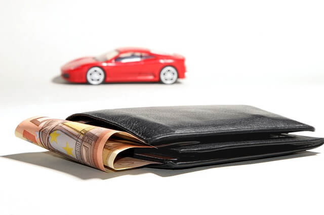 Portemonnaie mit Geldscheinen und im Hintergrund ein Spielzeugauto