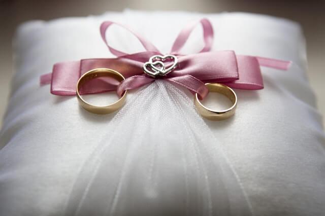 2 goldene Eheringe auf einem weißen Kissen