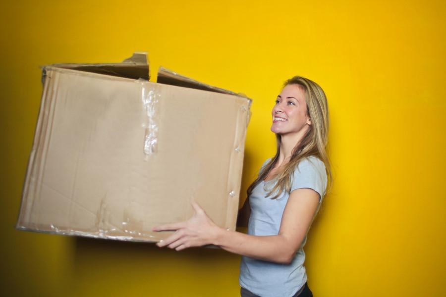 Frau hält einen Umzugskarton in der Hand